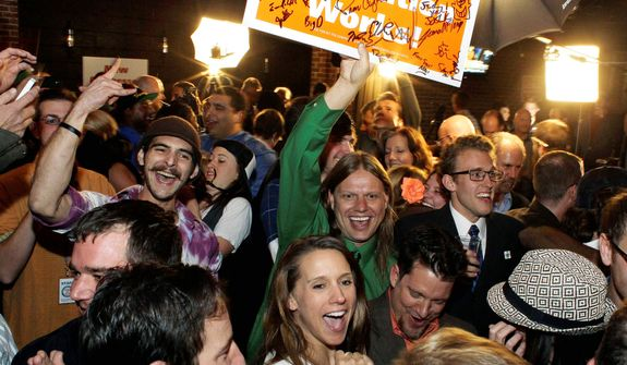 People attending an Amendment 64 watch party in a bar in Denver on Nov. 6, 2012, celebrate after a local television station announced the marijuana amendment's passage. The amendment would make it legal in Colorado for individuals to possess and for businesses to sell marijuana for recreational use. (Associated Press)