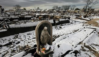 ** FILE ** A religious statue stands in the fire-scorched landscape of Breezy Point after a Nor'easter snowstorm on Nov. 8, 2012, in New York. The beachfront neighborhood was devastated during Superstorm Sandy when a fire pushed by the raging winds destroyed many homes. (Associated Press)
