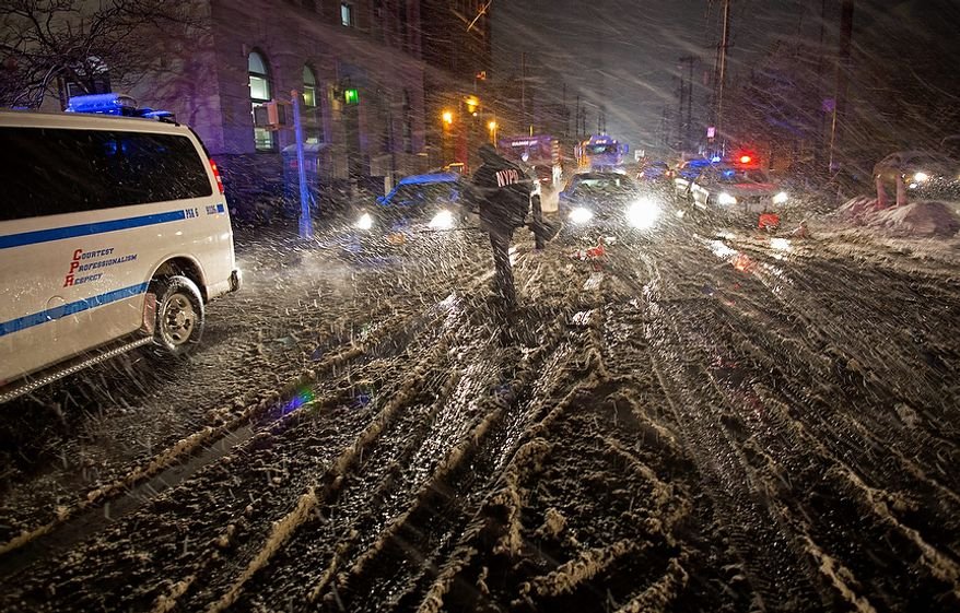 A member of the New York Police Department walks through snow as it accumulates in the Rockaway Beach neighborhood of the borough of Queens, New York, Wednesday, Nov. 7, 2012, in the wake of Superstorm Sandy. A Noreaster is complicating an already difficult situation with wind and blowing snow. (AP Photo/Craig Ruttle)