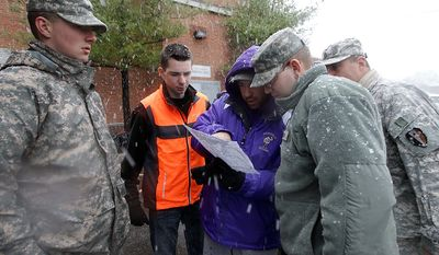 Volunteers Chris Braistch center, huddles with National Guardsmen and fellow volunteer Zach Vorisek as they plan a route to distribute donated blankets to residents without power as a nor'easter approached in the wake of Superstorm Sandy, Wednesday, Nov. 7, 2012, in Little Ferry, N.J. (AP Photo/Kathy Willens)