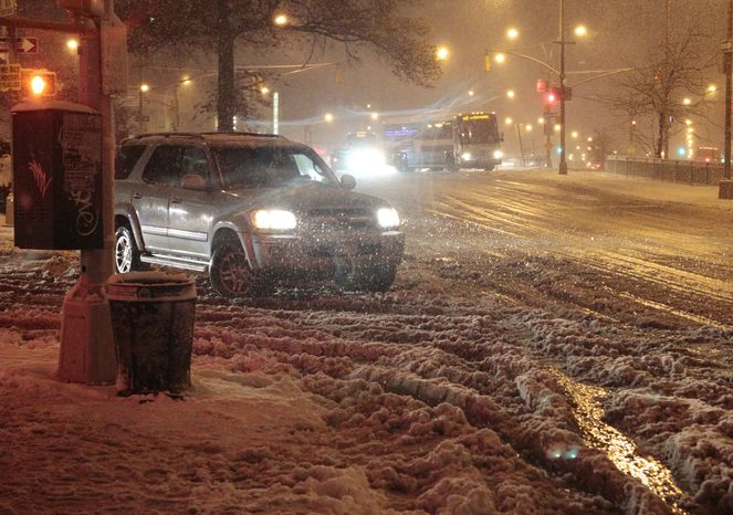 Cars navigate Queens Boulevard during a snow storm on Nov. 7, 2012, in the Queens borough of New York. Coastal residents of New York and New Jersey faced new warnings to evacuate their homes and airlines canceled hundreds of flights as the storm arrived only a week after Superstorm Sandy left dozens dead and millions without power. (Associated Press)