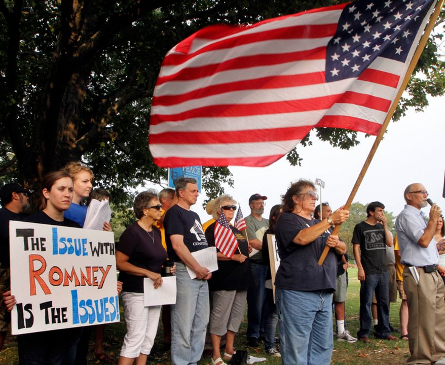**FILE** Tea Party activists protest Sept. 4, 2011, against Republican presidential candidate Mitt Romney at a Tea Party Express rally in Concord, N.H. (Associated Press)