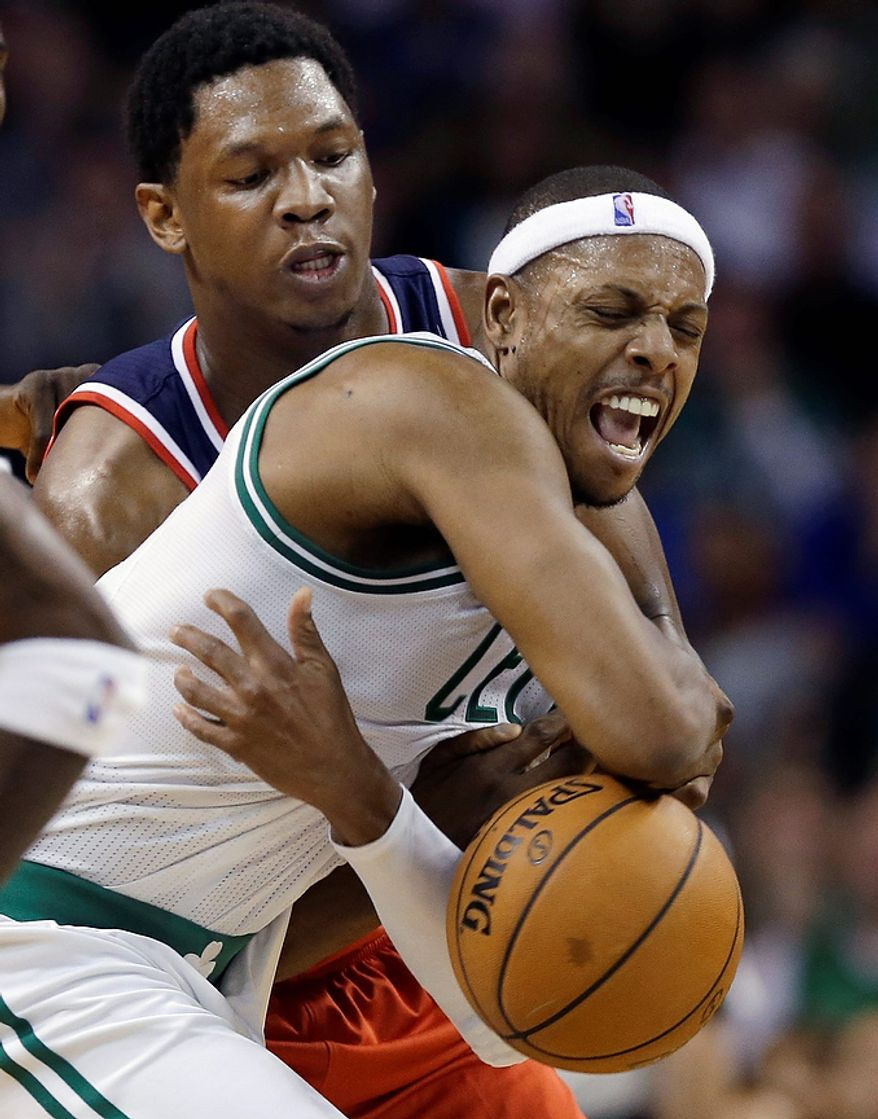 Boston Celtics forward Paul Pierce is grabbed and fouled from behind by Washington Wizards forward Kevin Seraphin after Pierce stole the ball from Seraphin during the second half of an NBA basketball game in Boston, Wednesday, Nov. 7, 2012. The Celtics won 100-94 in overtime. (AP Photo/Elise Amendola)