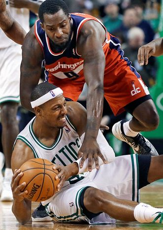 Boston Celtics forward Paul Pierce protects the ball on the floor against Washington Wizards forward Martell Webster (9) after recovering a loose ball during the second half of an NBA basketball game in Boston, Wednesday, Nov. 7, 2012. The Celtics won 100-94 in overtime. (AP Photo/Elise Amendola)
