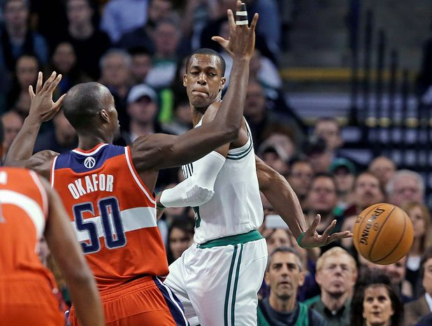 Boston Celtics guard Rajon Rondo passes the ball behind his back against the defense of Washington Wizards center Emeka Okafor (50) during the first half of an NBA basketball game in Boston, Wednesday, Nov. 7, 2012. (AP Photo/Elise Amendola)