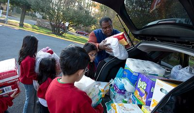 Children from the St. Andrew Apostle Catholic Church school in Silver Spring, Md., help parishioner Rick Gross load his SUV with baby products to take to New Jersey for victims of Superstorm Sandy on Nov. 9, 2012. The church, which also sent a passenger van full of clothes, cleaning products and toiletries, plans to hold a toy drive as well. (Barbara L. Salisbury/The Washington Times)