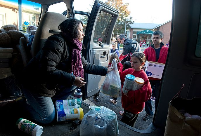 Soley Somma (left) of Wheaton, Md., a parishioner at St. Andrew the Apostle Catholic Church in Silver Spring, Md., loads donations into a passenger van Nov. 9, 2012. These items, along with clothes, toiletries and baby products, will be taken to St. Benedict Church in Holmdel, N.J., for victims of Hurricane Sandy. Somma, a former Brooklyn resident, says that she was so moved by the devastation that she saw on the news that she told her husband she was going to take a van and drive to New York. (Barbara L. Salisbury/The Washington Times)