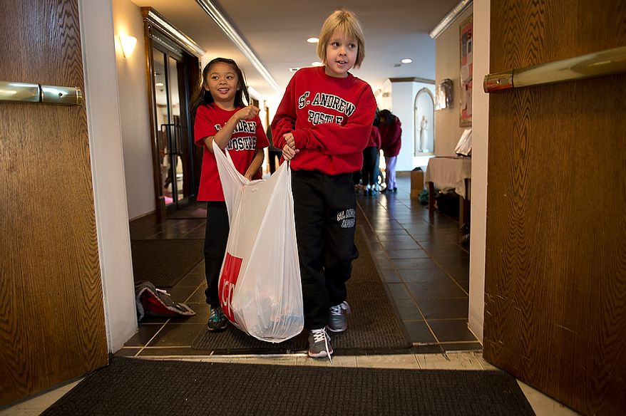 Ginger Sejismundo (left), 5, and Isabella Merino, 8, both students at St. Andrew the Apostle Catholic School in Silver Spring, Md., carry a big bag of candy out of their church to a passenger van that will take donated items to St. Benedict Church in Holmdel, N.J., for victims of Superstorm Sandy. (Barbara L. Salisbury/The Washington Times)
