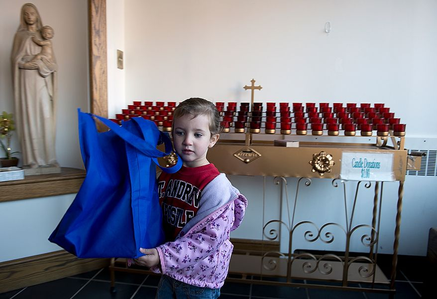 Angelina Trigiani, 3, of Brookeville, Md., carries a bag of donated items from St. Andrew the Apostle Catholic Church in Silver Spring, Md., to a passenger van that will deliver them to a church in Holmdel, N.J., for victims of Superstorm Sandy on Nov. 9, 2012. (Barbara L. Salisbury/The Washington Times)
