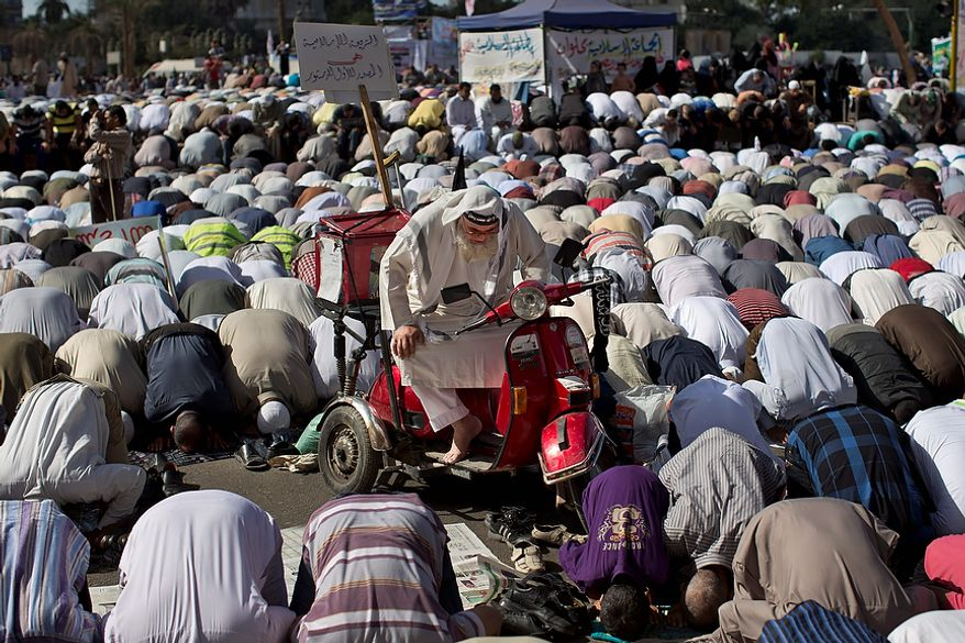 """Egyptian Muslims pray a Nov. 9, 2012, rally in Tahrir Square in Cairo. Thousands of ultraconservative Muslims rallied in the Egyptian capital, demanding the country's new constitution be based on the rulings of Islamic law, or Shariah. The poster on the the motor scooter reads in Arabic, """"Islamic law is the first source of the constitution."""" (Associated Press)"""