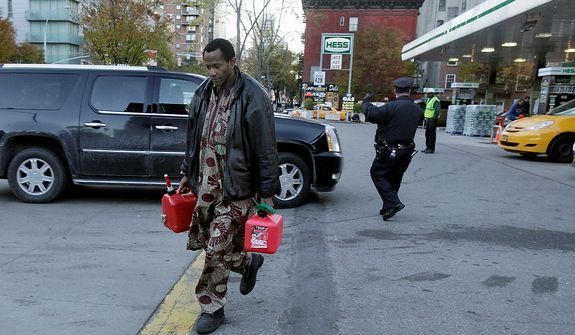 A man carries two filled gas cans at a gasoline station in New York on Nov. 9, 2012. Fuel shortages and distribution delays that occurred after Superstorm Sandy and a nor'easter hit the region led to gas hoarding, prompting New York City and Long Island to initiate an even-odd gas rationing plan. (Associated Press)