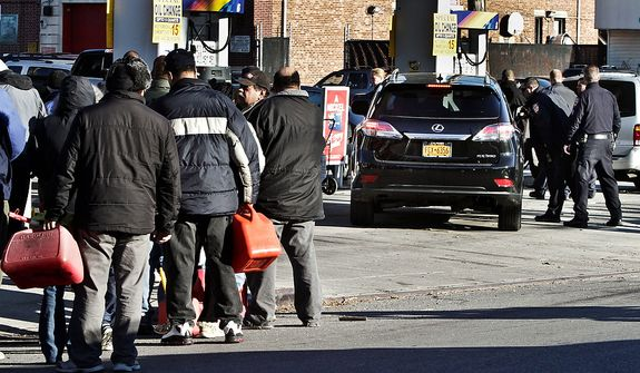 Police direct cars to pumps while people stand in line with containers for gas in the Brooklyn borough of New York on Nov. 9, 2012. Fuel shortages and distribution delays that occurred after Superstorm Sandy and a nor'easter hit the region led to gas hoarding, prompting New York City and Long Island to initiate an even-odd gas rationing plan. (Associated Press)