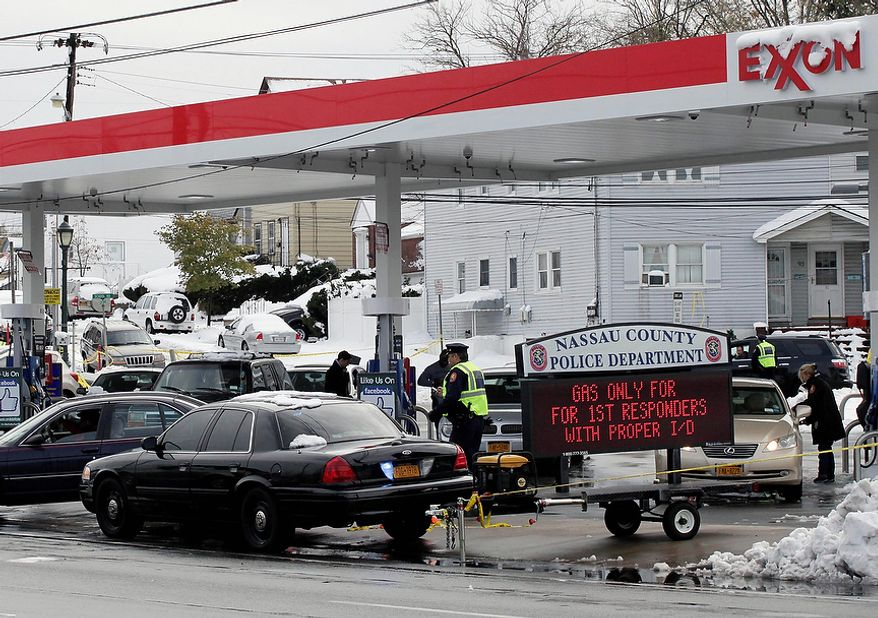Nassau County Police control access to an Exxon station in Elmont, N.Y., on Nov. 8, 2012. Fuel shortages and distribution delays that occurred after Superstorm Sandy and a nor'easter hit the region led to gas hoarding, prompting New York City and Long Island to initiate an even-odd gas rationing plan. (Associated Press)