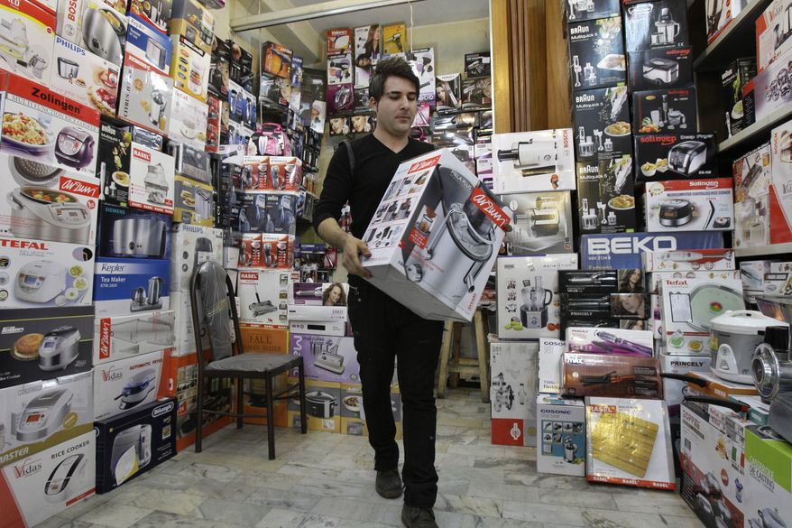 **FILE** Iranian shopkeeper Masoud Hatami works at a home appliance store in Tehran on Nov. 8, 2012. (Associated Press)