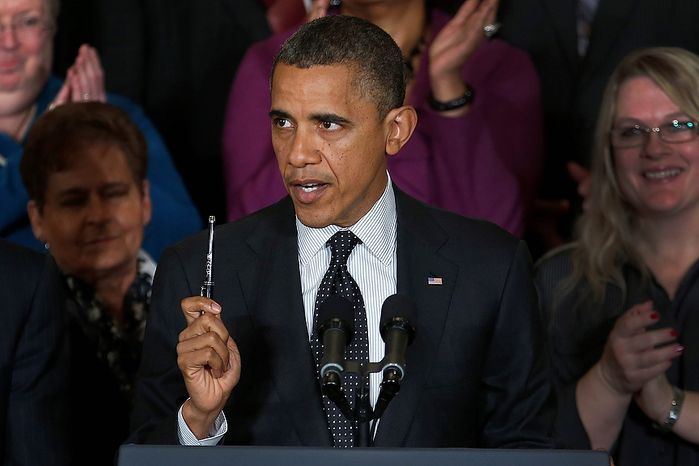 President Obama holds up a pen as he speaks about the economy and the deficit Nov. 9, 2012, in the East Room of the White House in Washington. (Associated Press)
