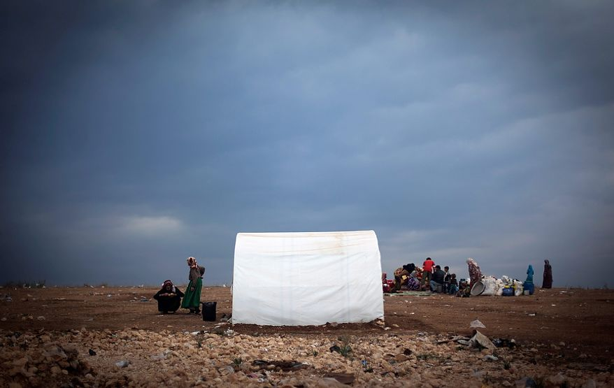 Syrian families who fled from the violence in their villages sit Nov. 8, 2012, next to their belongings at a displacement camp in the Syrian village of Atmeh, near the Turkish border. (Associated Press)