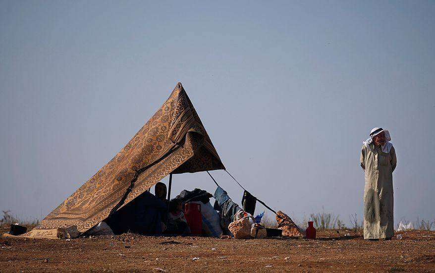 A Syrian family who fled from the violence in their village sits Nov. 5, 2012, in a tent at a displacement camp in the Syrian village of Atmeh, near the Turkish border. (Associated Press)