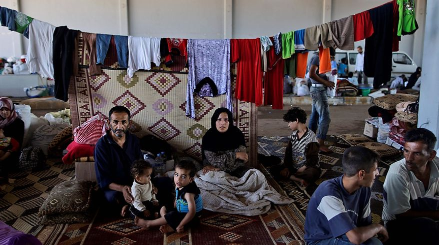 A Syrian family, who fled their home due to government shelling, takes refuge Sept. 13, 2012, at Bab Al-Salameh crossing border, hoping to cross to one of the refugee camps in Turkey, near the Syrian town of Azaz. (Associated Press)