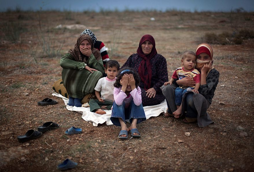 A Syrian family who fled from the violence in their village sit on the ground at a displacement camp in the Syrian village of Atmeh, near the Turkish border. (Associated Press)