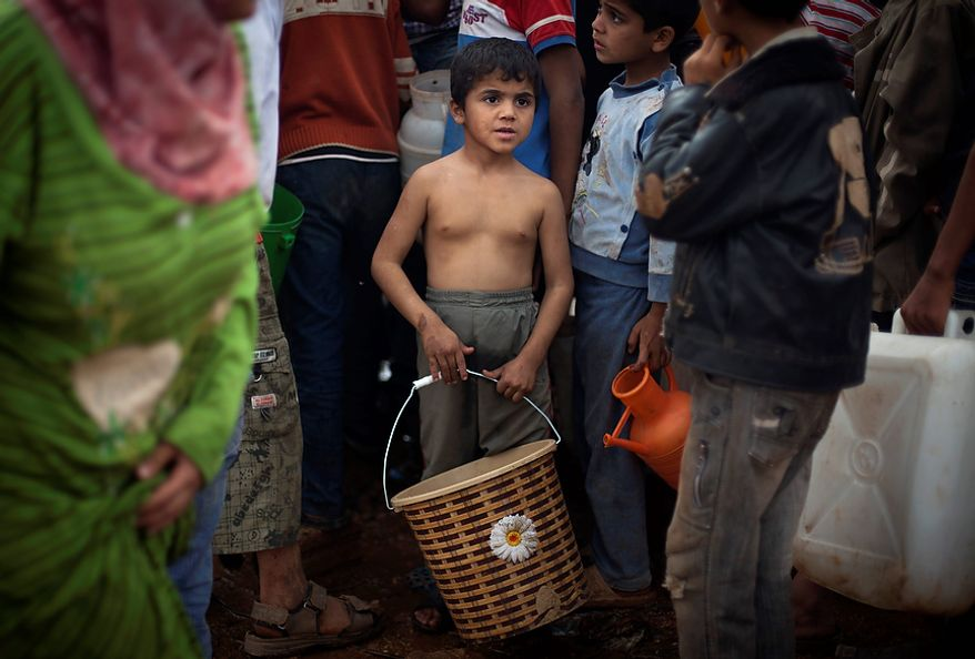 A Syrian boy who fled with his family from the violence in their village waits his turn Nov. 8, 2012, to fill water at a displacement camp, in the Syrian village of Atmeh, near the Turkish border. (Associated Press)