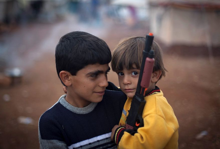 Two Syrian boys, both of whom fled with their families from the violence in their village, look on Nov. 8, 2012, as one holds a gun toy at a displacement camp in the Syrian village of Atmeh, near the Turkish border. (Associated Press)