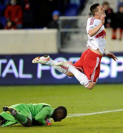 New York Red Bulls forward Kenny Cooper (right) sails over D.C. United  goalkeeper Bill Hamid during the second half of an MLS Eastern Conference semifinal playoff soccer game on Nov. 8, 2012, in Harrison, N.J. D.C. United defeated the Red Bulls, 1-0, to advance to the next round. (Associated Press)