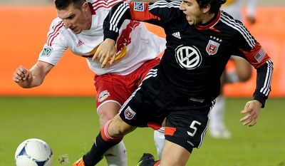 New York Red Bulls forward Kenny Cooper (left) battles for control of the ball with D.C. United defender Dejan Jakovic during the second half of an MLS Eastern Conference semifinal playoff soccer game on Nov. 8, 2012, in Harrison, N.J. D.C. United defeated the Red Bulls, 1-0, to advance to the next round. (Associated Press)