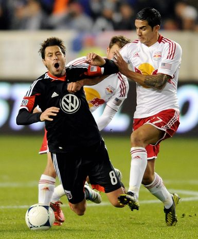 New York Red Bulls midfielder Tim Cahill (right) pushes D.C. United midfielder Branko Boskovic during the first half of an MLS Eastern Conference semifinal playoff soccer match on Nov. 8, 2012, in Harrison, N.J. (Associated Press)