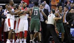 Milwaukee Bucks point guard Brandon Jennings, second from right, is restrained by referee Mike Callahan (24) as a scuffle breaks out against the Washington Wizards after a flagrant foul by Wizards guard Bradley Beal on Bucks guard Monta Ellis during the second half of an NBA basketball game on Friday, Nov. 9, 2012, in Washington. The Bucks won 101-91. (AP Photo/Nick Wass)