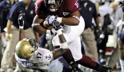 Troy running back D.J. Taylor (31) runs over the a tackle by Navy safety Kwazel Bertrand (17) during the second half of an NCAA college football game in Troy, Ala., Saturday, Nov. 10, 2012. Troy won 41-31. (AP Photo/The (Troy) Messenger, Thomas Graning)