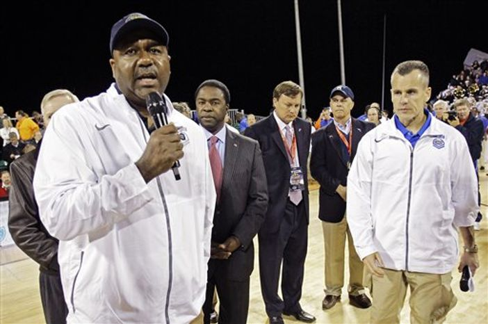 Georgetown head coach John Thompson III, left, speaks to the fans as Florida head coach Billy Donovan, right, watches while they announce the cancellation of the Navy-Marine Corps Classic NCAA college basketball game due to heavy condensation on the court aboard the USS Bataan at the Mayport Naval Station, Friday, Nov. 9, 2012, in Jacksonville, Fla. (AP Photo/John Raoux)