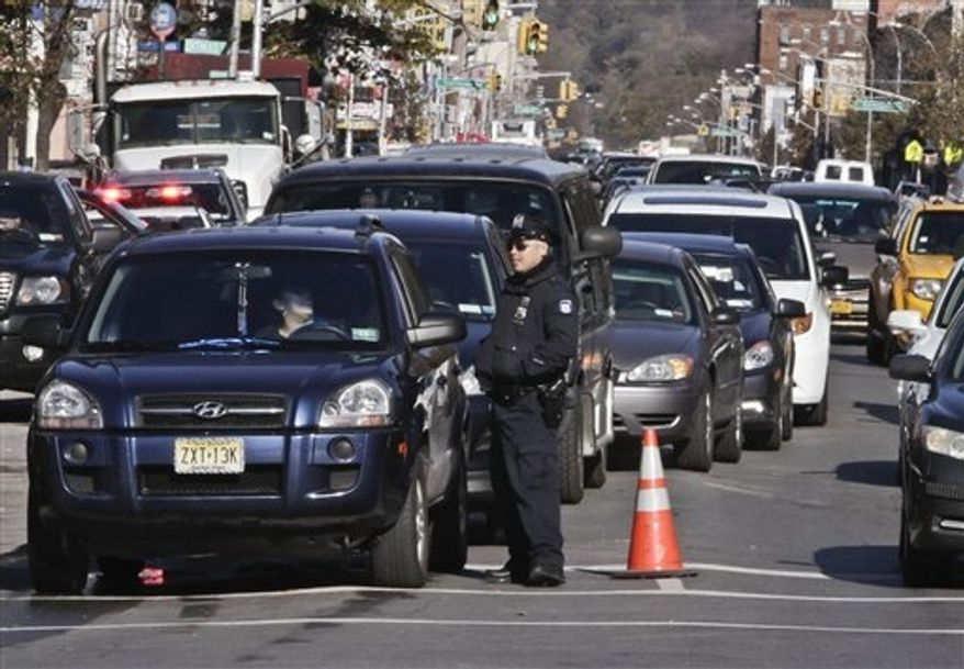 Police direct cars to gas pumps outside a gas station on Friday, Nov. 9, 2012, in the Brooklyn borough of New York. Police were at gas stations to enforce a new gasoline rationing plan that lets motorists fill up every other day that started in New York on Friday morning. (AP Photo/Bebeto Matthews)