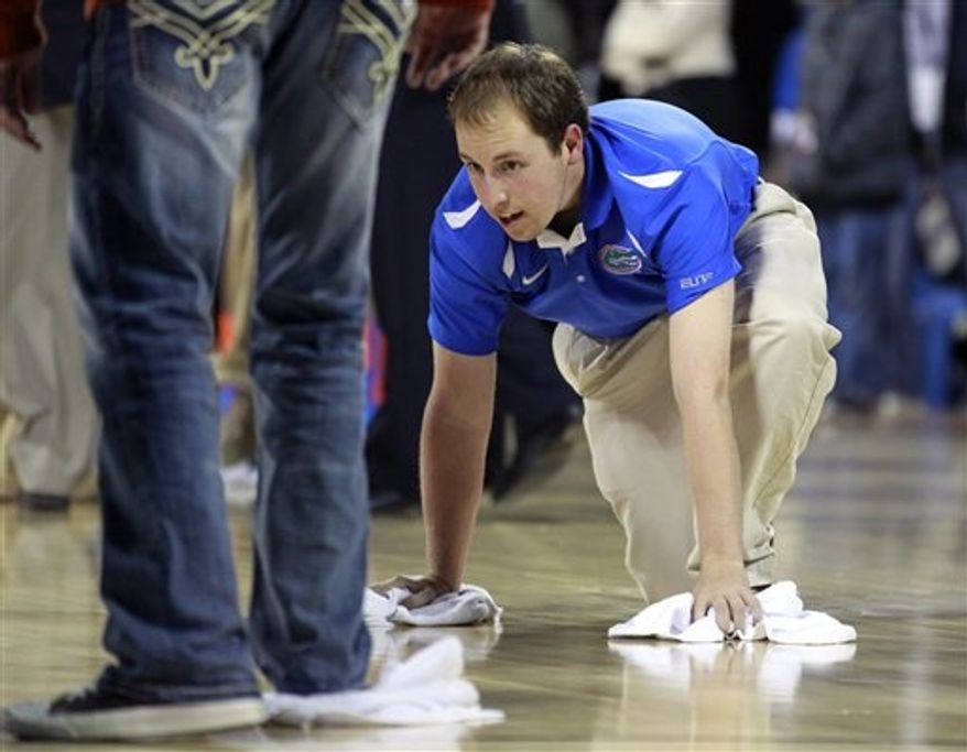 Workers try to dry the basketball court before the second half of the Navy-Marine Corps Classic NCAA college basketball game between Florida and Georgetown aboard the USS Bataan at the Mayport Naval Station, Friday, Nov. 9, 2012, in Jacksonville, Fla. The game was canceled due to condensation on the court. (AP Photo/John Raoux)
