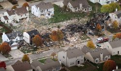 This aerial view shows two homes that were leveled and numerous neighboring homes that were damaged by a massive explosion that sparked a huge fire and killed two people late Saturday night into Sunday in Indianapolis. The blast shattered windows, crumpled walls and could be felt at least three miles away. (Associated Press)