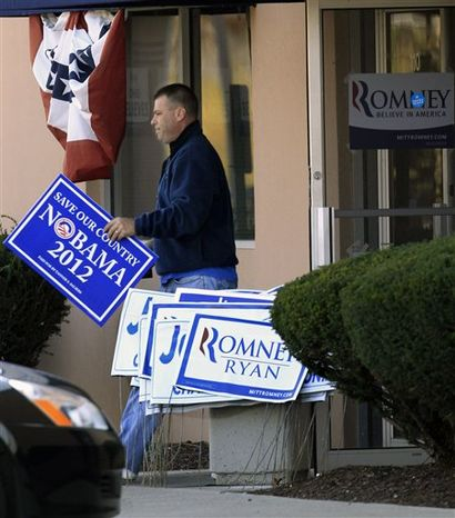 A man walks out of the Ohio headquarters of Mitt Romney campaign office carrying a Nobama 2012 sign, Wednesday, Nov. 7, 2012, in Columbus, Ohio. R