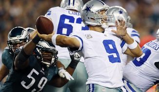 Dallas Cowboys quarterback Tony Romo, right, passes under pressure from Philadelphia Eagles middle linebacker DeMeco Ryans in the first half of an NFL football game, Sunday, Nov. 11, 2012, in Philadelphia. (AP Photo/Julio Cortez)