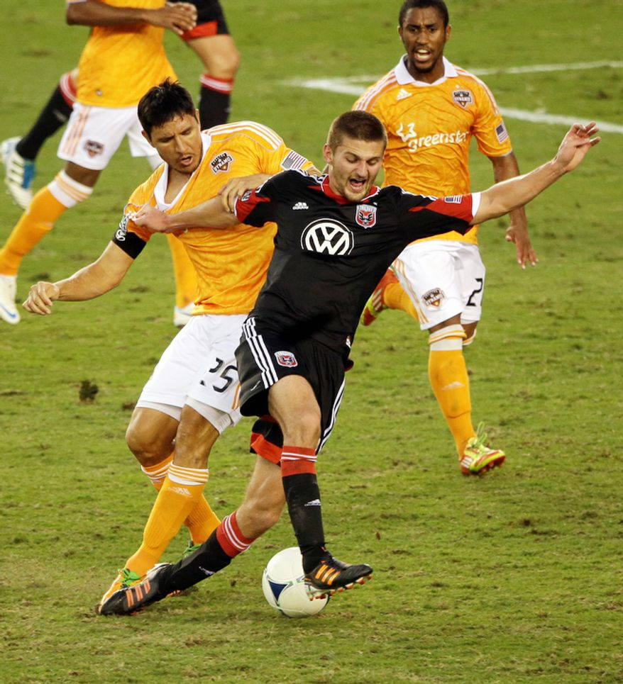 Houston Dynamo's Brian Ching (25) battles D.C. United's Perry Kitchen, right, for the ball during the second half of an MLS Eastern Conference Championship soccer game, Sunday, Nov. 11, 2012, in Houston. The Dynamo defeated D.C. United 3-1. (AP Photo/David J. Phillip)