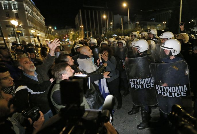 Greek riot police officers, right, push the last remaining protesters off the street, following an anti-austerity rally in front of the Parliament in central Athens, Sunday, Nov. 11, 2012. Thousands of protesters converged on the Greek capital's main square outside the Parliament on Sunday evening, as lawm