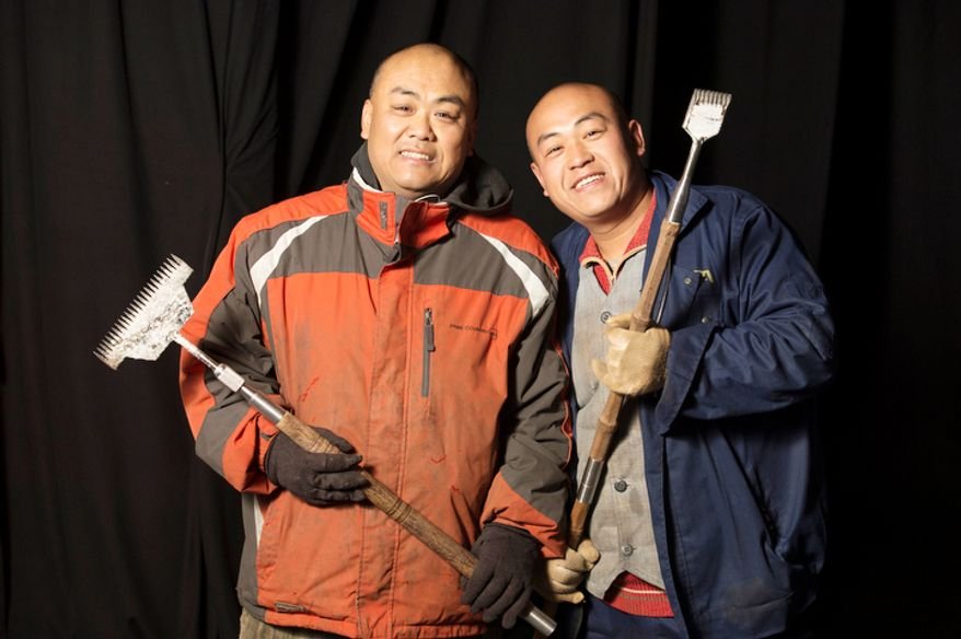 Wang Lian Hai. 39, (left) and his brother Wang Lian Jun, 35, (right) are two of the 40 artisan ice sculptors from Harbin, China,  working on the construction of the attraction ICE! featuring DreamWorks Shrek the Halls at the Gaylord National Resort & Convention Center in National Harbor, Md. They are from Harbin, China, the capital city of China's northernmost province, Heilongjiang, across the border from Siberia, Russia. Harbin, China has been host of the Ice and Snow Festival for more than 25 years, welcoming approximately 800,000 visitors annually.  (Rod Lamkey Jr./The Washington Times)