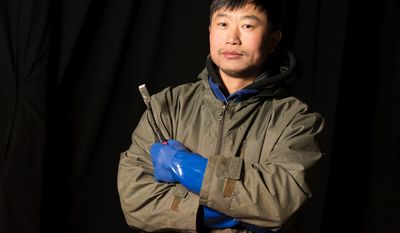 Wei Xiang Ji, 39, is one of the 40 artisan ice sculptors from Harbin, China,  working on the construction of the attraction ICE! featuring DreamWorks Shrek the Halls at the Gaylord National Resort & Convention Center in National Harbor, Md.  (Rod Lamkey Jr./The Washington Times)