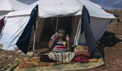 An elderly and disabled Syrian man who fled from the violence in his village prays Nov. 10, 2012, in front of his tent at a displaced persons camp in the Syrian village of Atma, near the Turkish border. (Associated Press)