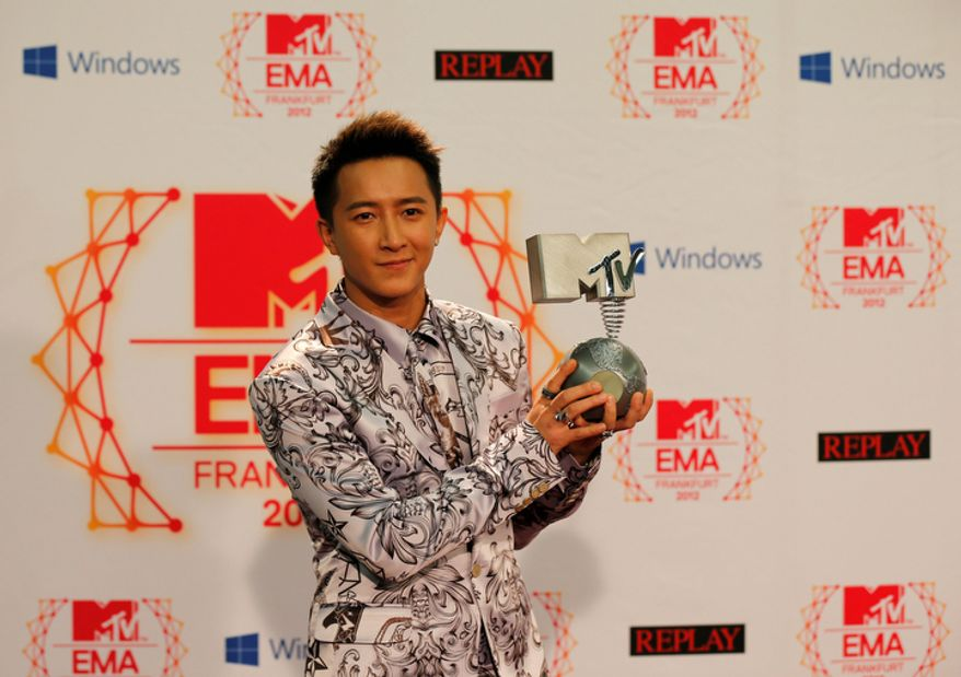 Chinese singer Han Geng presents his award as Best Worldwide Act during the 2012 MTV European Music Awards show at the Festhalle in Frankfurt, central Germany, Sunday, Nov. 11, 2012. (AP Photo/Frank Augstein)