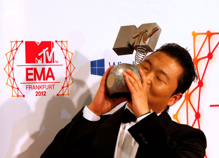 South Korean Psy presents his award for the best video during the 2012 MTV European Music Awards show at the Festhalle in Frankfurt, central Germany, Sunday, Nov. 11, 2012. (AP Photo/Frank Augstein)