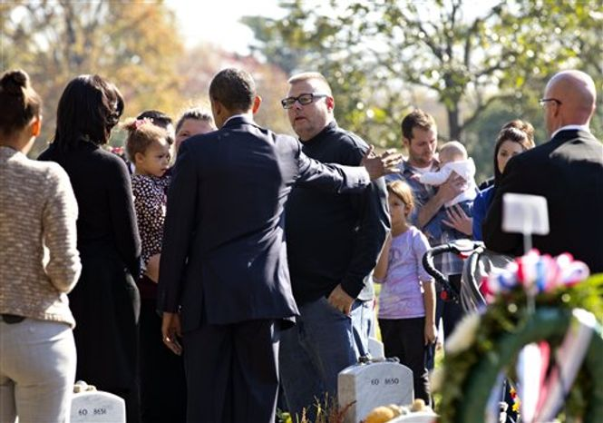 While at Arlington National Cemetery for Veterans Day ceremonies, President Obama and first lady Michelle Obama visited Section 60, the site where many of America's most recent war dead from the Afghanistan and Iraq conflicts are buried, in Arlington, Va., Sunday, Nov. 11, 2012. (AP Photo/J. Scott Applewhite)