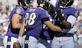 Baltimore Ravens tight end Dennis Pitta, center, celebrates his touchdown with teammates in the first half of an NFL football game against the Oakland Raiders in Baltimore, Sunday, Nov. 11, 2012. (AP Photo/Nick Wass)