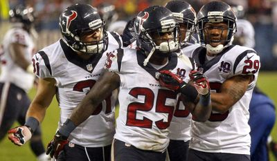 Houston Texans cornerback Kareem Jackson (25) celebrates his interception against the Chicago Bears with teammates Shiloh Keo (31) and Glover Quin (29) during the first half an NFL football game, Sunday, Nov. 11, 2012, in Chicago. (AP Photo/Charles Rex Arbogast)