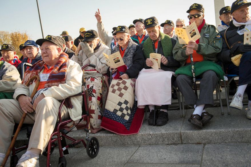World War II veterans arrive and take their seats as the sun rises during the Veterans Day at the National World War II Memorial. (Rod Lamkey Jr./The Washington Times)