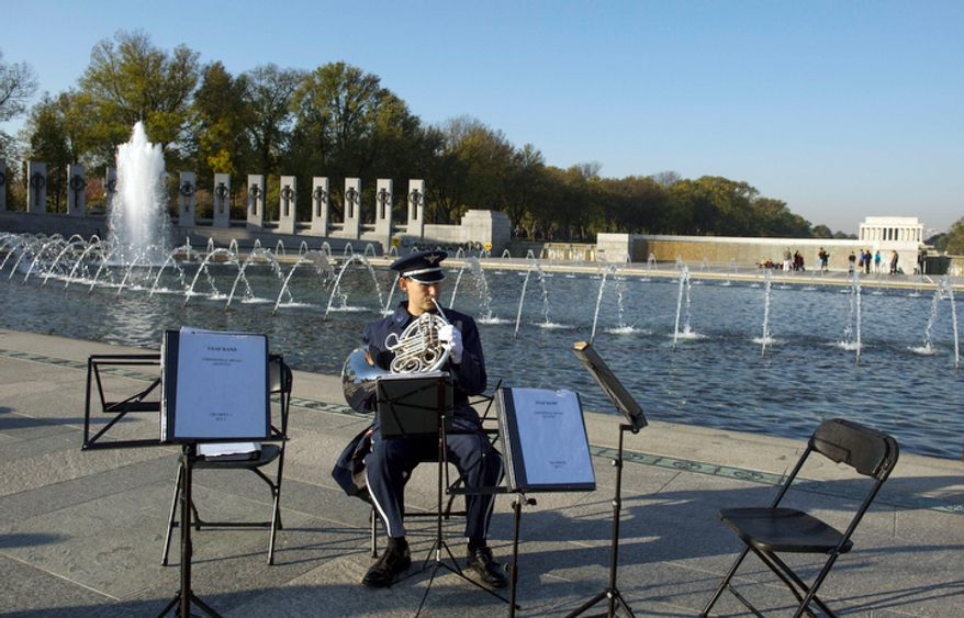 US Air Force Band Master Sargent Brett Miller warms up prior to the Veterans Day at the National World War II Memorial event. (Rod Lamkey Jr./The Washington Times)