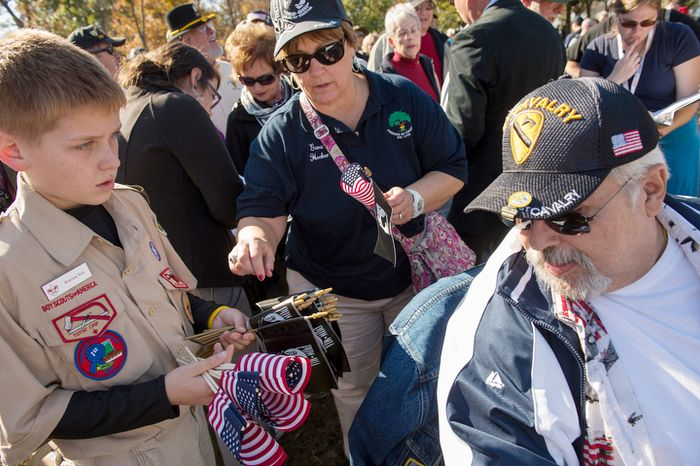 Boy Scout Brayton Tetz, 11, of Herndon, Va., (left) passes out US flags and POW-MIA flags to veterans and others as they arrive for an event at the Vietnam Veterans Memorial during Veteran's Day weekend. (Rod Lamkey Jr./The Washington Times)