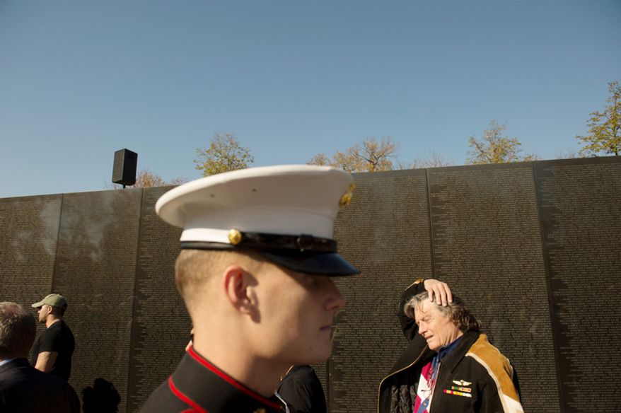Veterans and current service members walks along past the names on the wall at the Vietnam Veterans Memorial during Veteran's Day weekend in Washington, D.C. (Rod Lamkey Jr./The Washington Times)